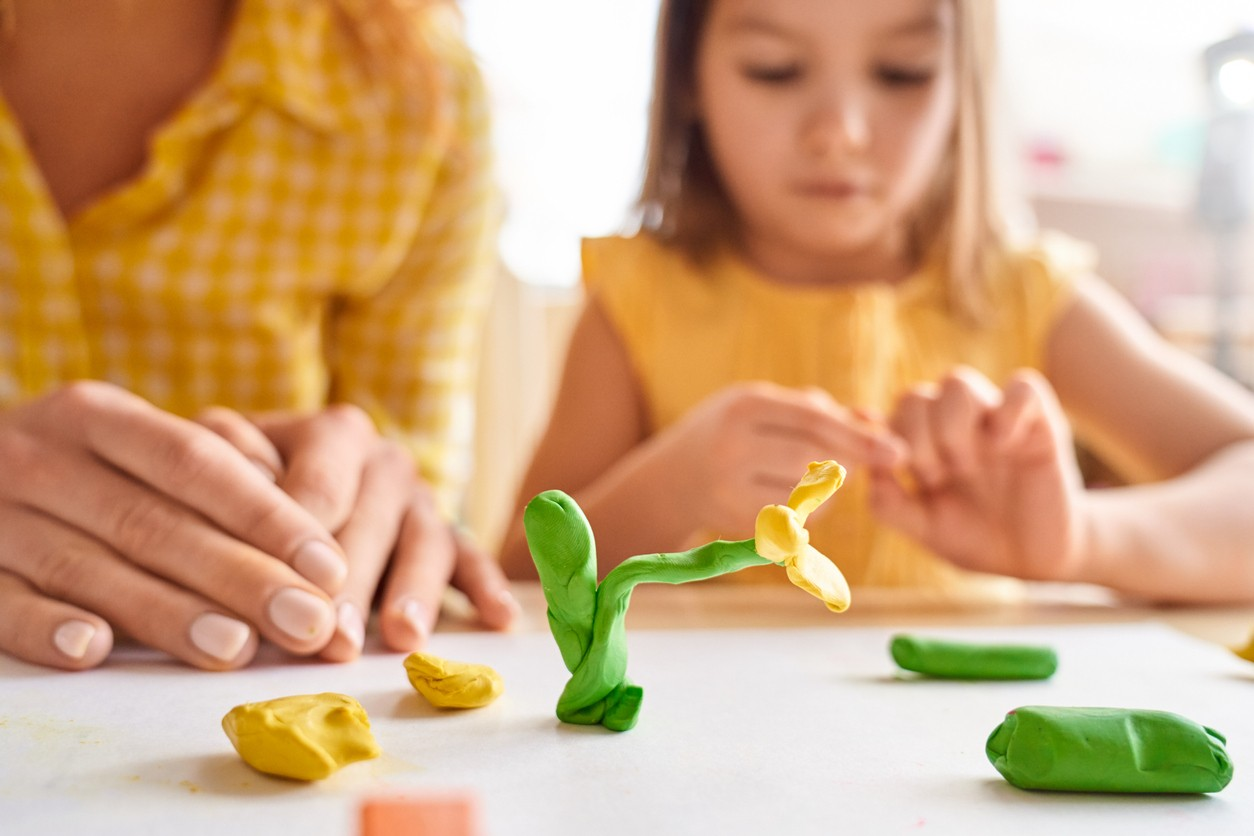 Young mother and her junior daughter playing with plasticine